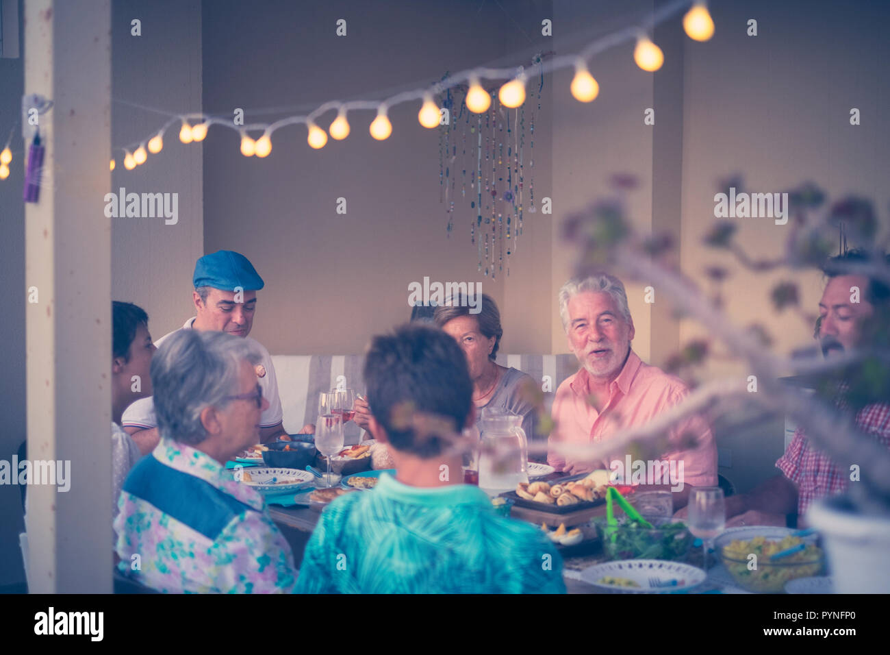 Group of people dining together at home on the terrace outdoor having fun and smile. friednship and friends event. Caucasian men and women with differ - Stock Image