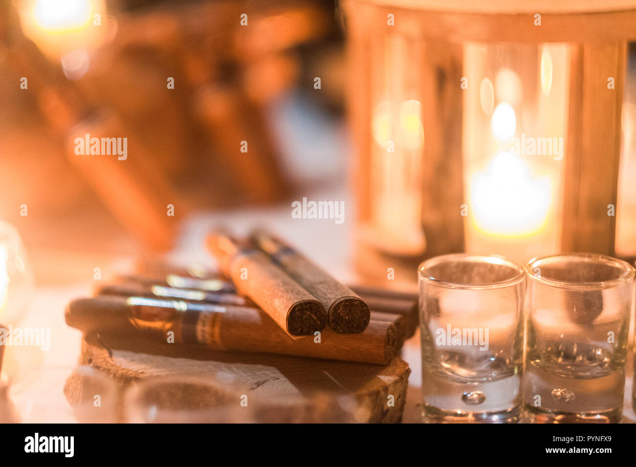 Cigar and rhum rum to end the night in friednship with men's things related. Bokeh and defocused image for conceptual mood about males - Stock Image