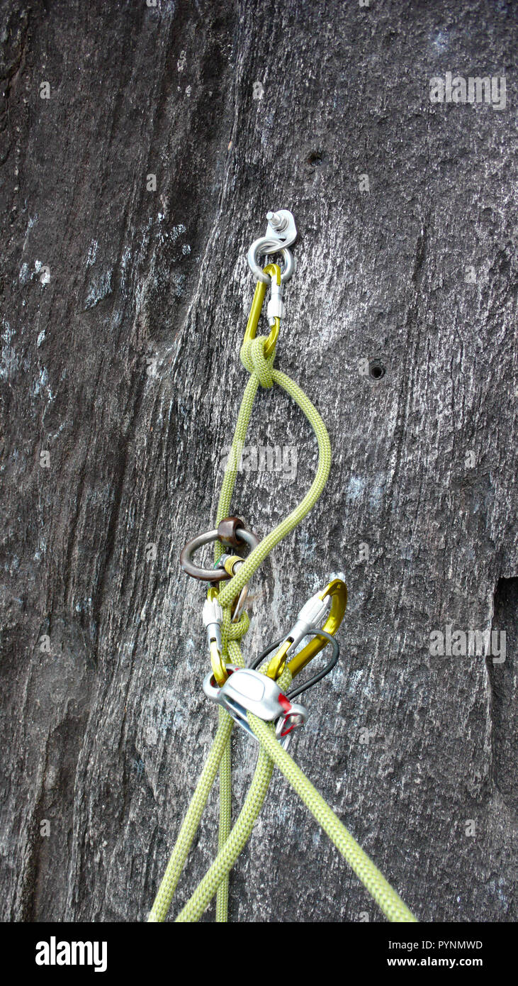 belay stance for rock climbing in black granite with bolts carabiners and a yellow rope - Stock Image