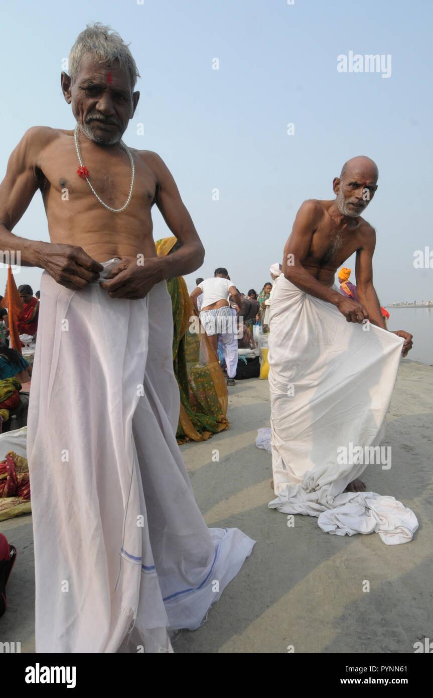 Two men drape their 'dhoti's' after taking a Makar-sankranti dip at Ganga Sagar where the holy river Ganga meets the Bay of Bengal, India. Photograph: - Stock Image