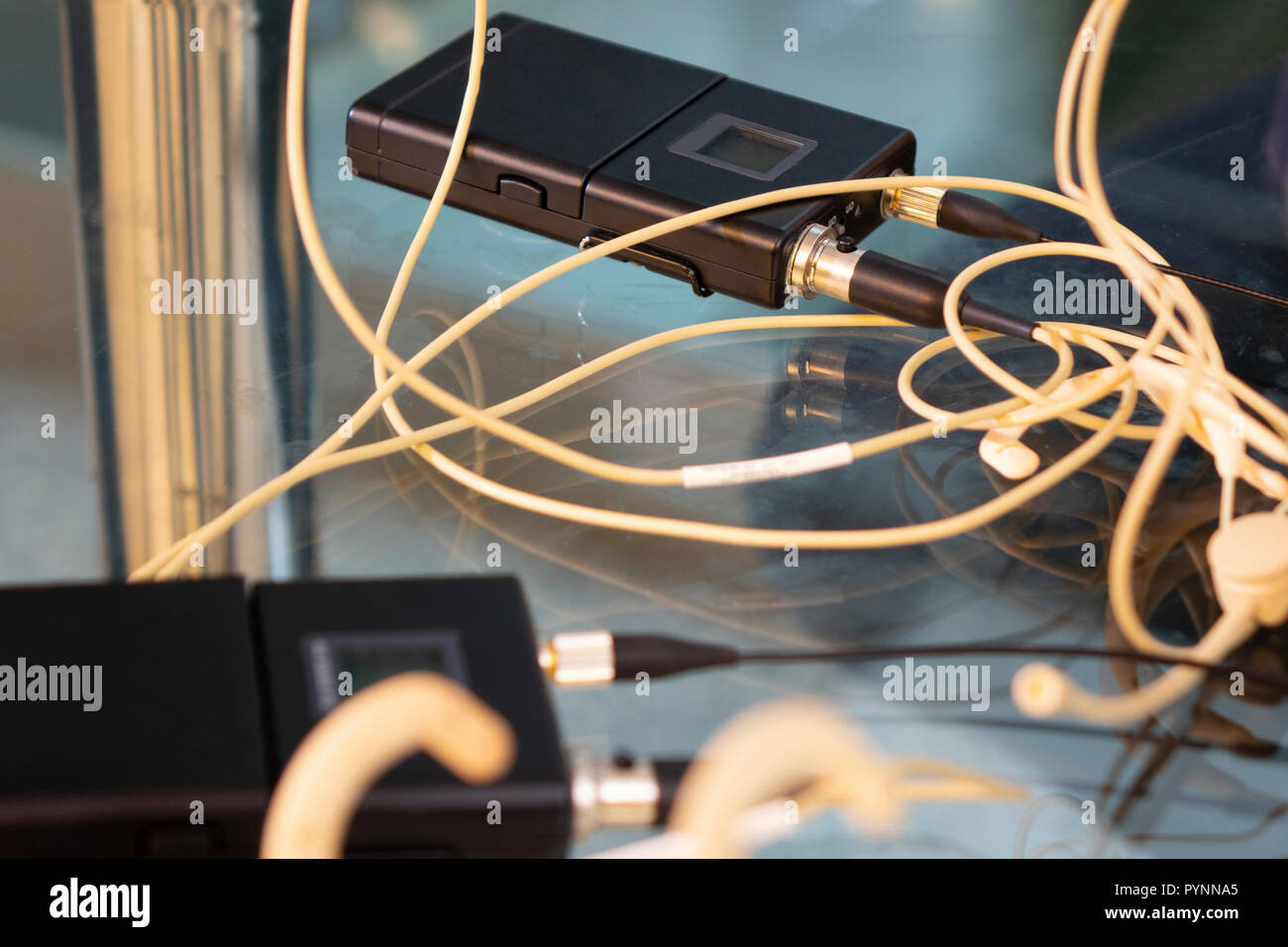 Head set wireless microphones transmitter and two wireless microphone reciever on glass table in tv studio - Stock Image