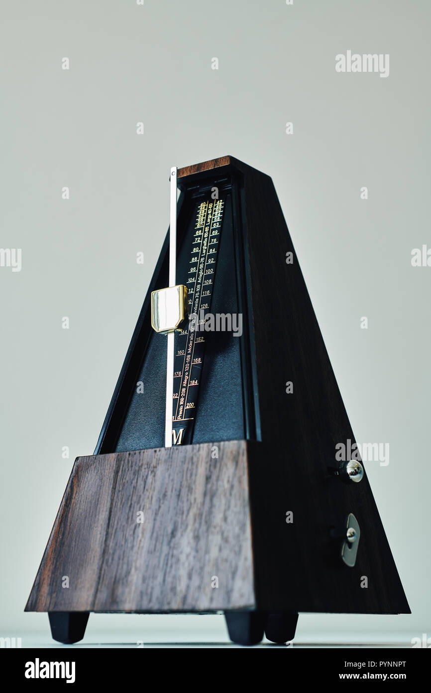 Vintage metronome, on a black background. - Stock Image