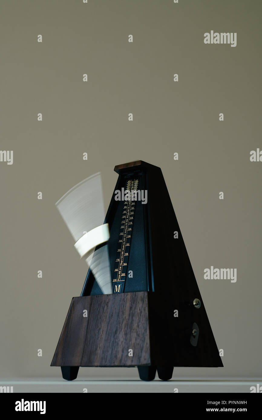 Vintage metronome, on a black background. Stock Photo