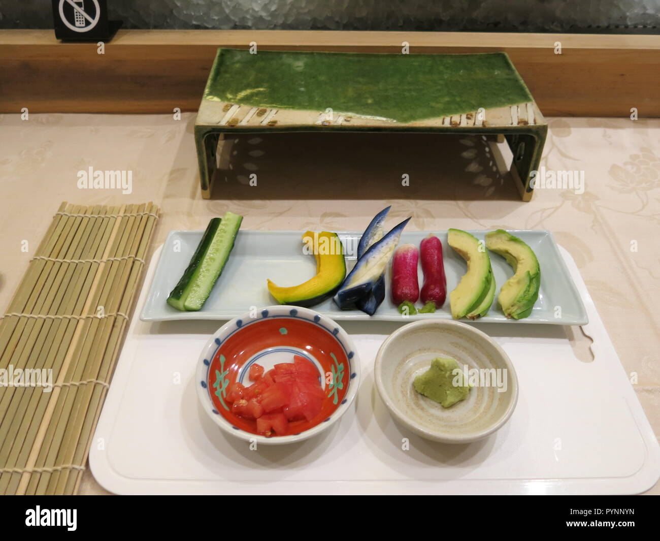 A dish of vegetable slices is prepared for the lunchtime sushi making at a Japanese restaurant. - Stock Image