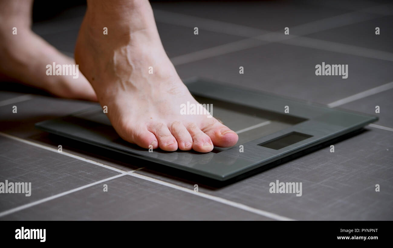 Male Feet On Glscales Menst Body Weight Close Up Stepping On Digital Scale Sport And Lifestyle Concept