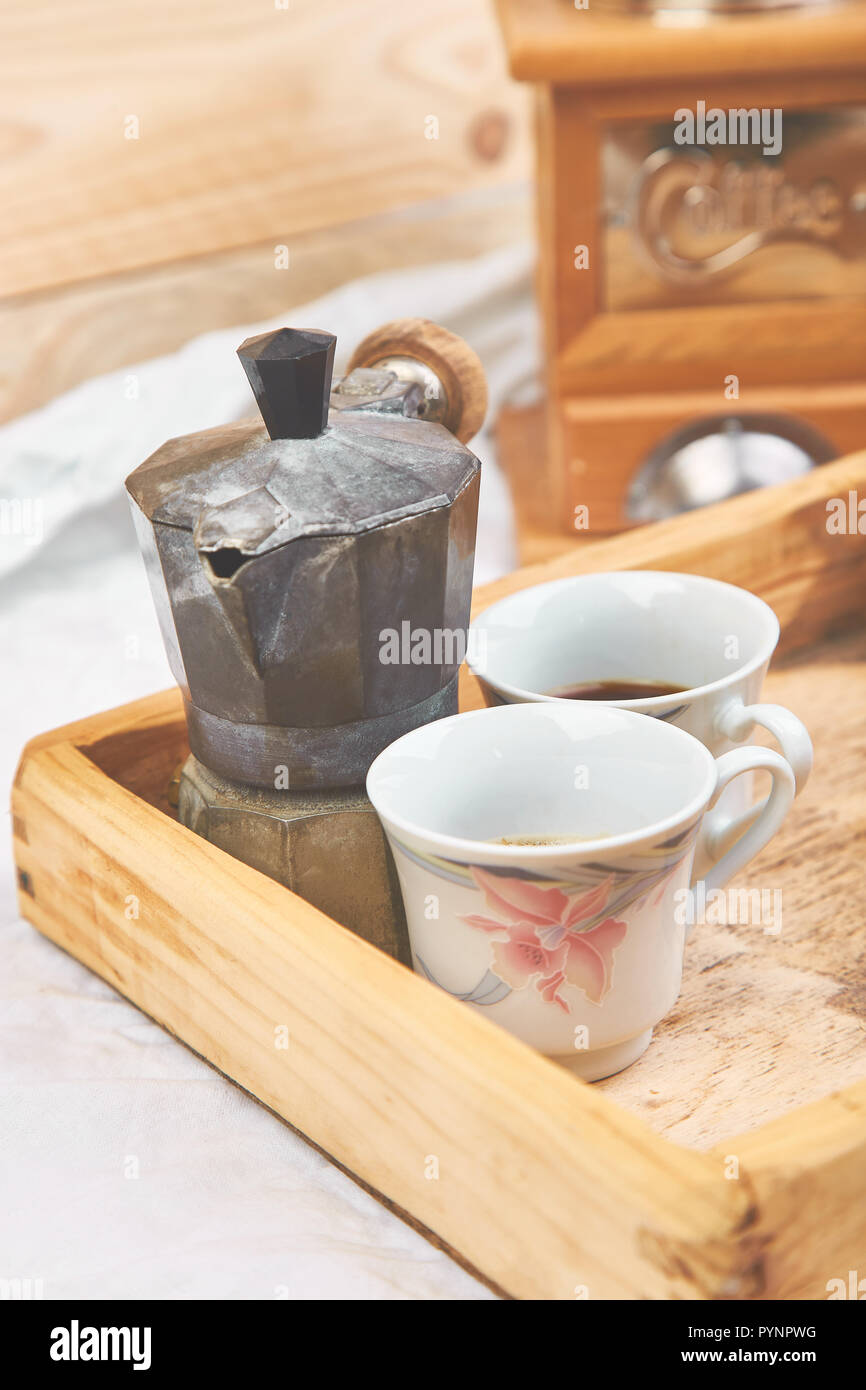 Moka coffee pot with two cup of coffe on wooden tray on white background. Old style italian coffee in soft vintage tone. Copy space. Stock Photo