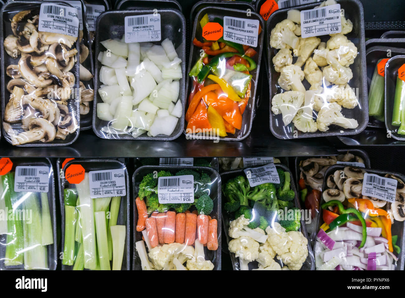 Prepared vegetables in shrink wrapped plastic on the shelves of a Canadian supermarket. - Stock Image