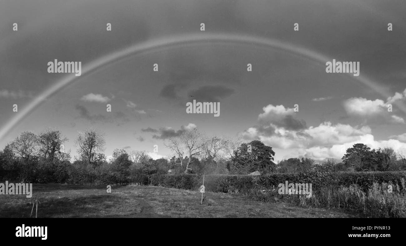 Black and white full complete rainbow over field, Lincolnshire, England, UK - Stock Image