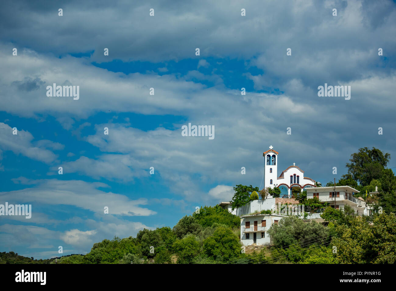 Spring daytime landscape with orthodox Christian church in the village of Mursi, Albania. Scenery cloudy sky with building located on top of green hill Stock Photo