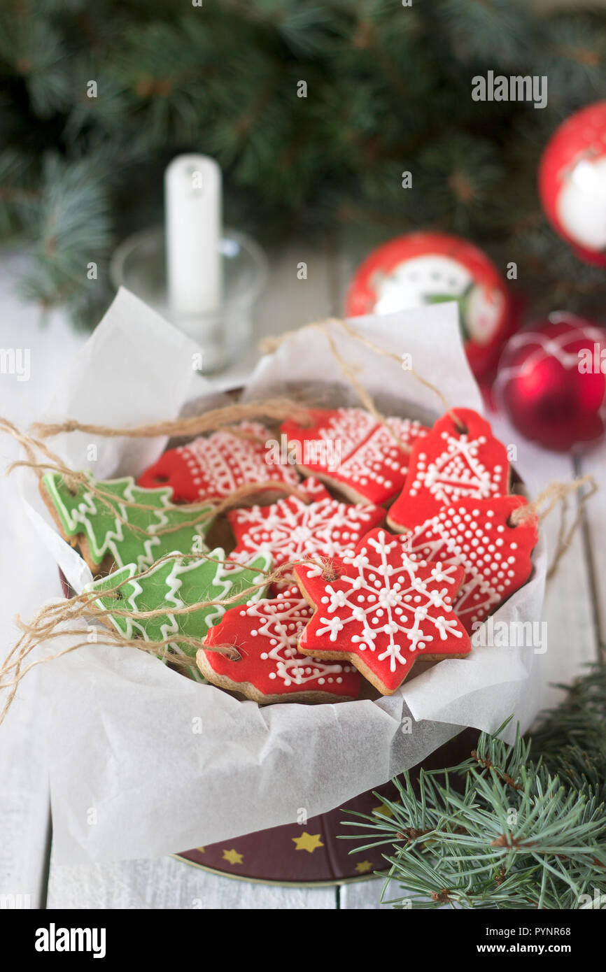 Gingerbread in a tin box in the background with Christmas toys, a candle and fir branches. Stock Photo