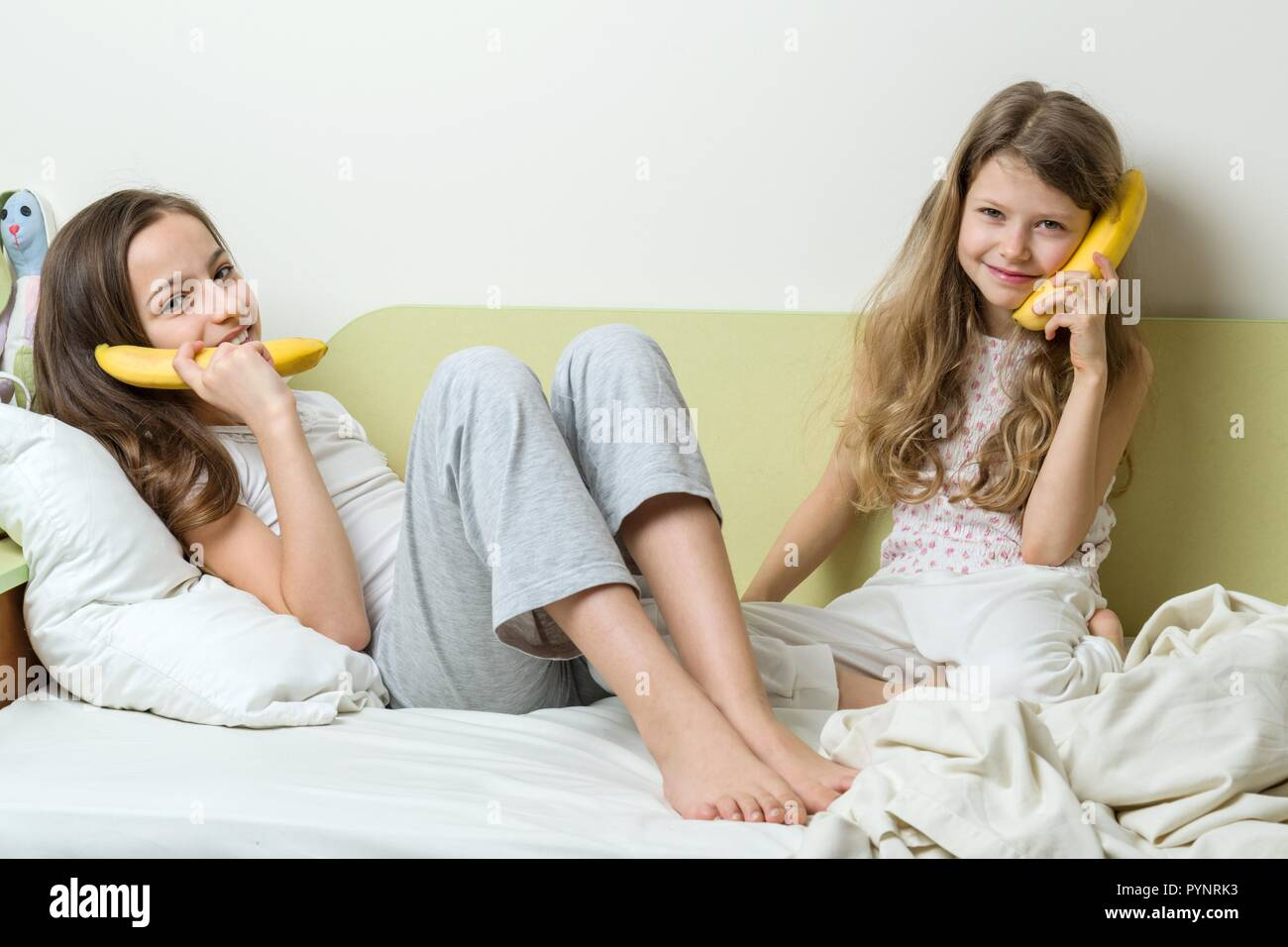 Two sister children in pajamas play in the morning in bed. Keep bananas as phones talking and laughing. - Stock Image