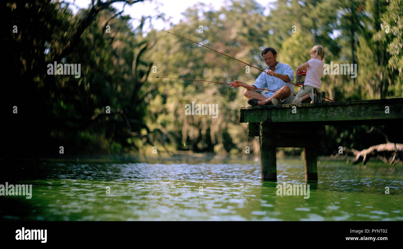 Mid-adult father fishing off a jetty with his young daughter. Stock Photo
