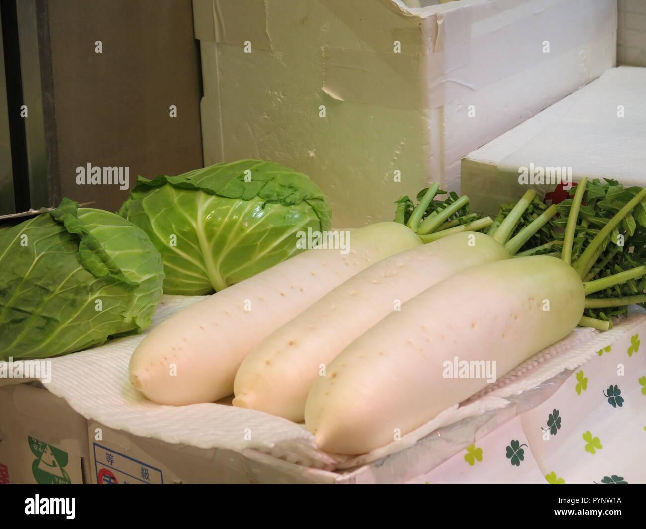 Three large white radishes in a Japanese street market - Stock Image
