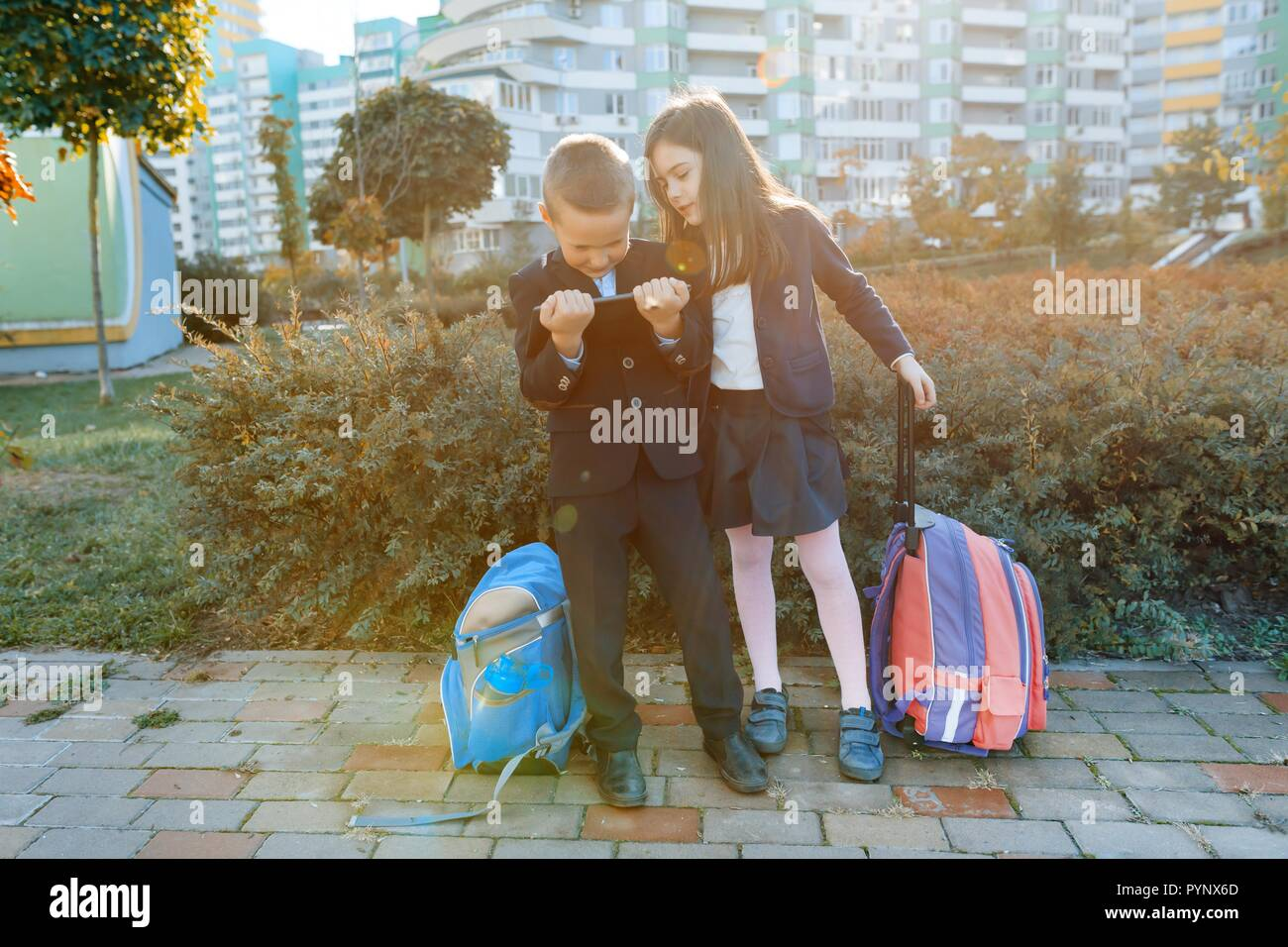 76496d2dc8ce Boy and girl pupils in primary school with a digital tablet. Outdoor  background, children