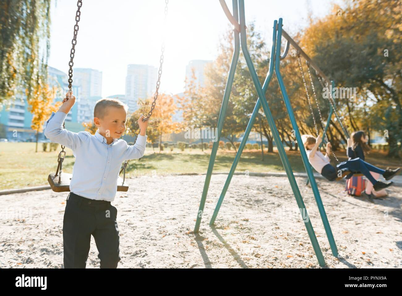 Children ride on a swing in autumn park. Focus on the boy, the girls in the distance, golden hour. Stock Photo