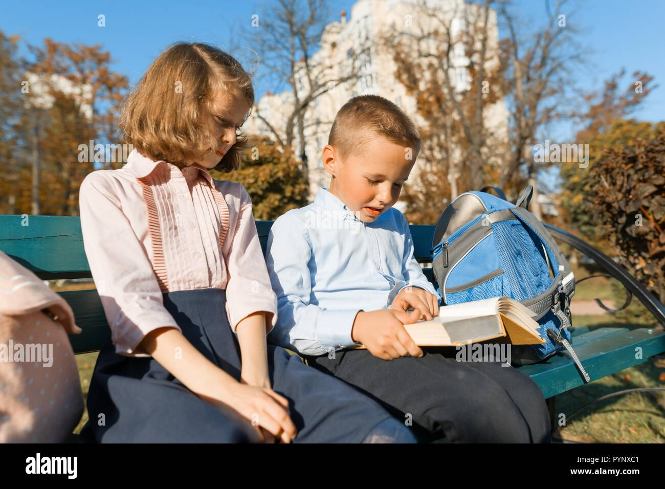 Little boy and girl schoolchildren read a book, sit on a bench, children with backpacks, bright sunny autumn day. Stock Photo