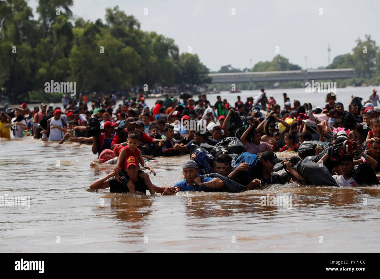 Tecun Uman, Guatemala. 29th Oct, 2018. Members of the second migrants' caravan, mostly Hondurans, cross the Suchiate river, which separates Guatemala and Mexico, in Tecun Uman, Guatemala, 29 October 2018. This is the second Central-American migrants caravan heading to the United States after past 13 October the first left San Pedro Sula. Credit: Esteban Biba/EFE/Alamy Live News - Stock Image