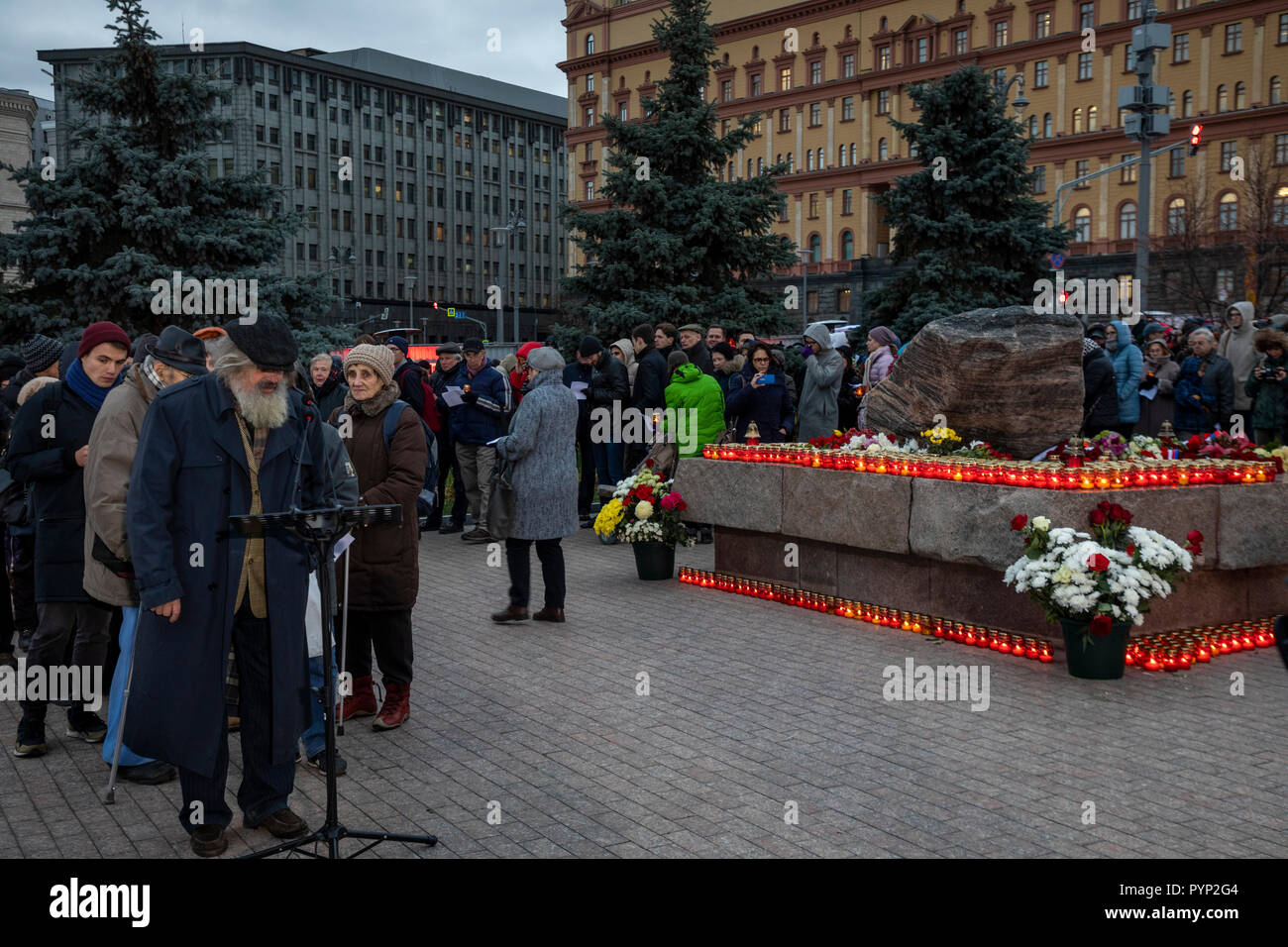 Moscow, Russia. 29th October, 2018 People lay flowers and light candles as they take part in an event commemorating the victims of political repression by the Solovetsky Stone monument in Lubyanka Square on the eve of Day of Remembrance of the Victims of Political Repression Credit: Nikolay Vinokurov/Alamy Live News - Stock Image