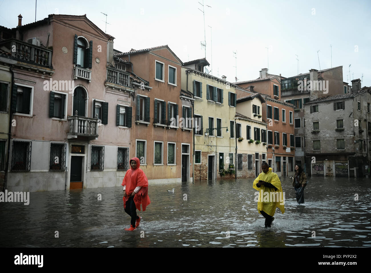 Venice, Italy. 29th October, 2018.Tourists wearing ponchos and wellies walk in high water during exceptional Acqua Alta - High Tide Floods in Venice, Italy on 29 October 2018. 70% of the lagoon city has been flooded by waters rising 149 centimetres above sea level. Credit: Piero Cruciatti/Alamy Live News - Stock Image