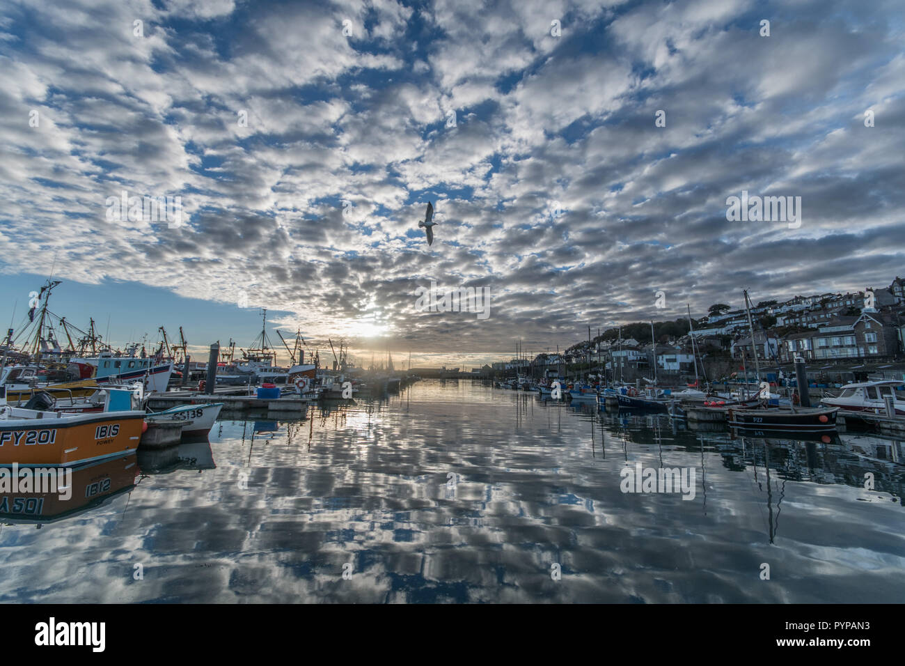Newlyn, Cornwall, UK. 30th Oct, 2018. UK Weather. Clouds reflecting in the calm water at Newlyn harbour in the early morning. Credit: Simon Maycock/Alamy Live News - Stock Image