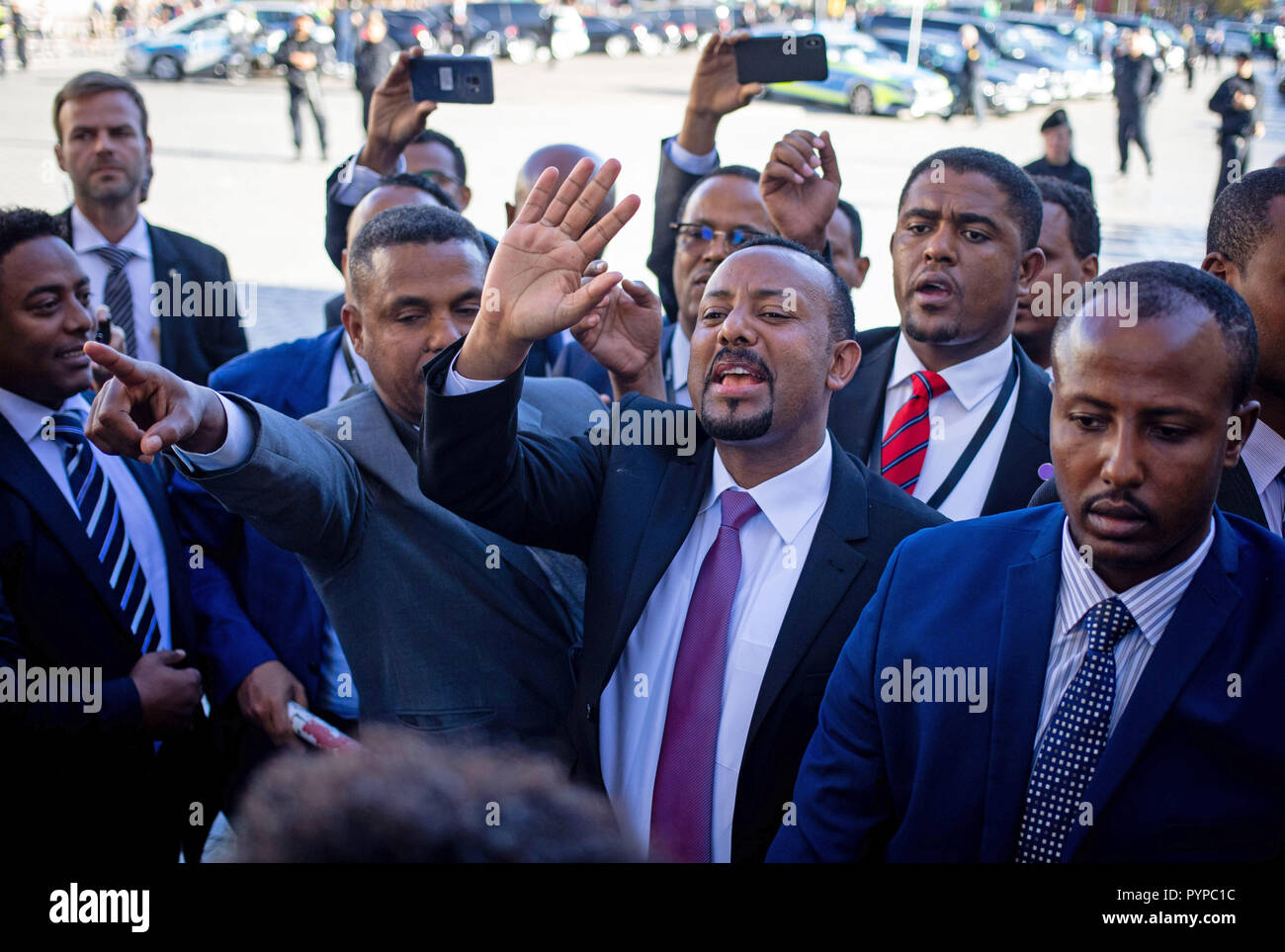 Berlin, Germany. 30th Oct, 2018. Abiy Ahmed Ali, Prime Minister of the Democratic Federal Republic of Ethiopia, waves to his supporters on Pariser Platz in front of the Brandenburg Gate. Eleven heads of state and government meet in the capital for the summit meeting. It is about an initiative for more private investment in Africa, which Merkel launched last year as President of the Group of Leading Economic Powers (G20). Credit: Kay Nietfeld/dpa/Alamy Live News - Stock Image