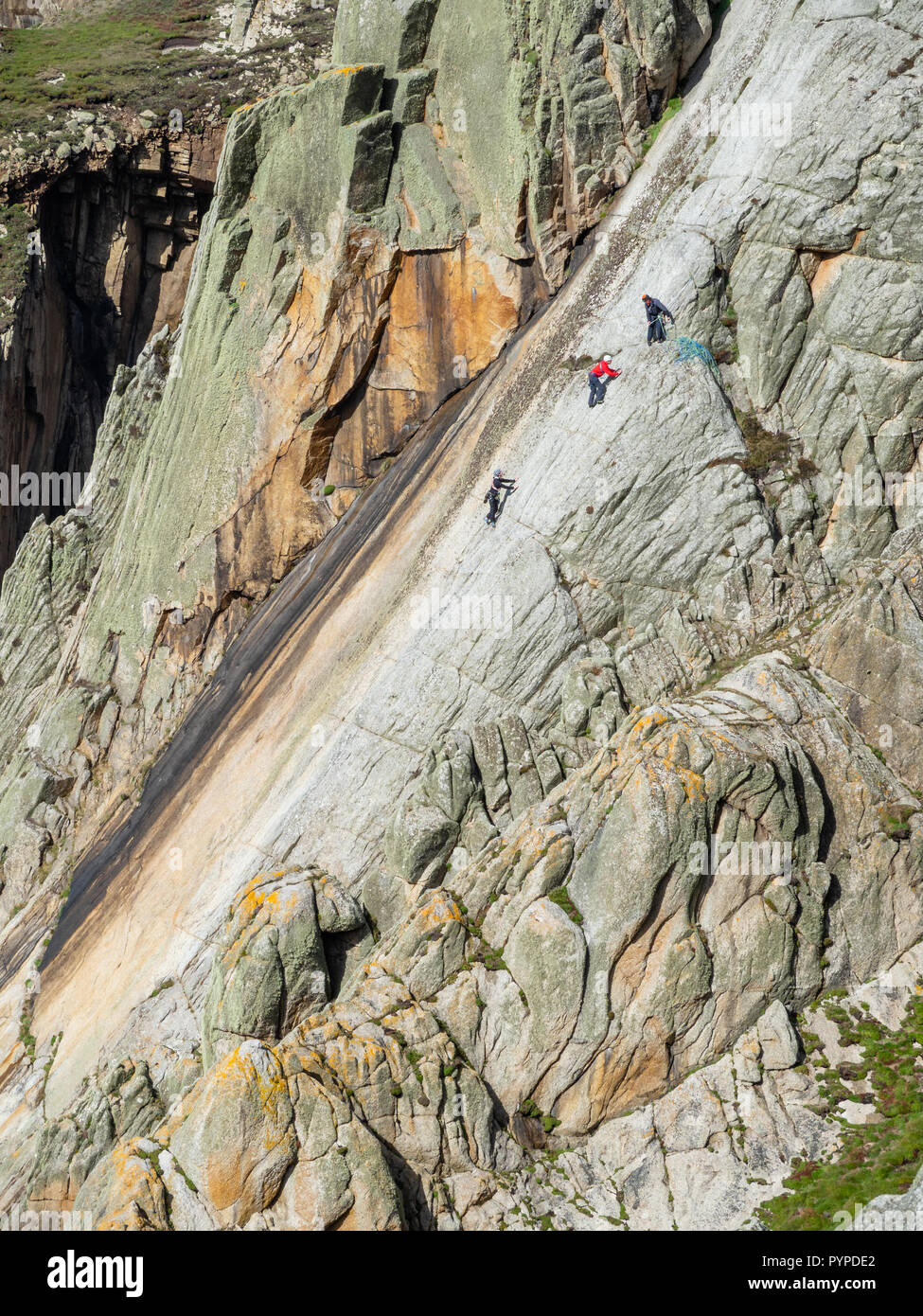 Climbers on the sheer face of The Devil's Slide the longest single granite slab climb in Europe - Lundy Island off Devon UK - Stock Image