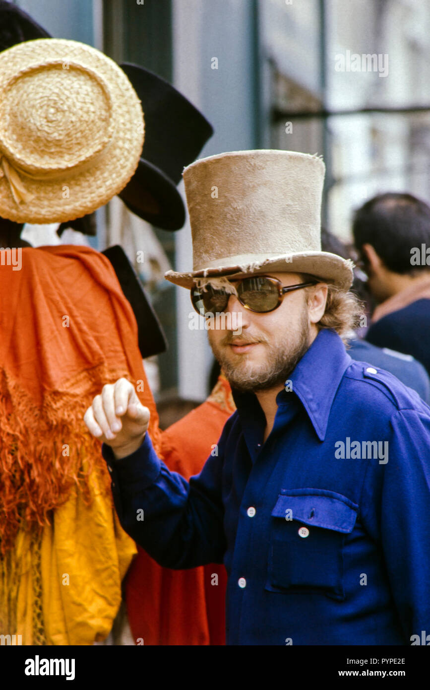 Hippy man wearing a top hat outside a hat shop in Portabello Road, London during the late 1960s Colin Maher/Simon Webster - Stock Image