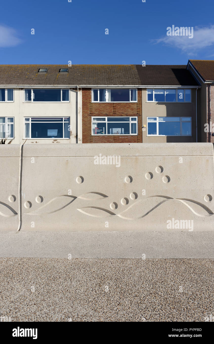 Pre cast concrete sea wall with Mythic Coast artwork, row of houses in background on Cleveleys promenade, part of coastal sea defences, fylde coast uk Stock Photo