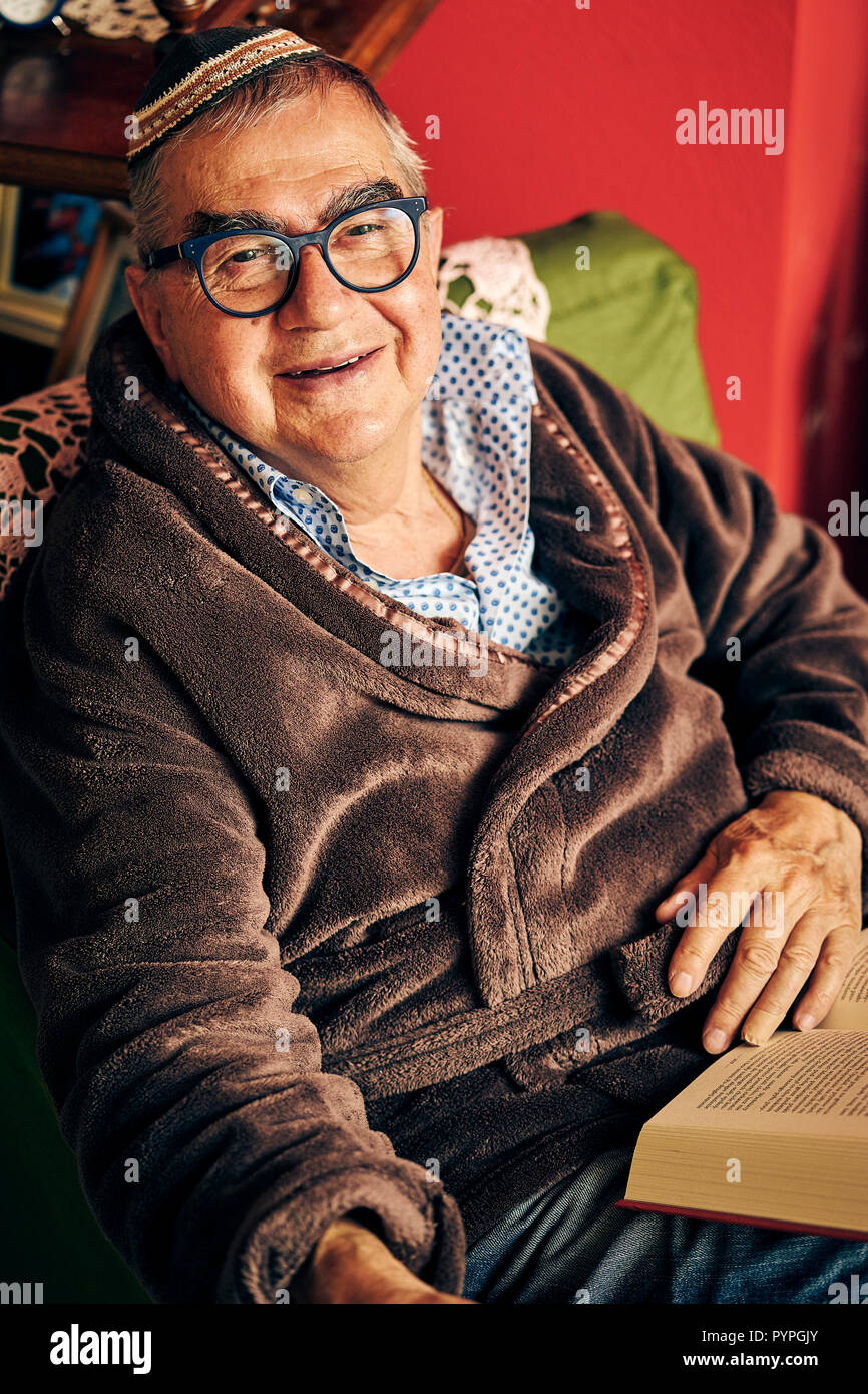 Jewish senior with glasses sitting in the armchair reading a torah book - Stock Image