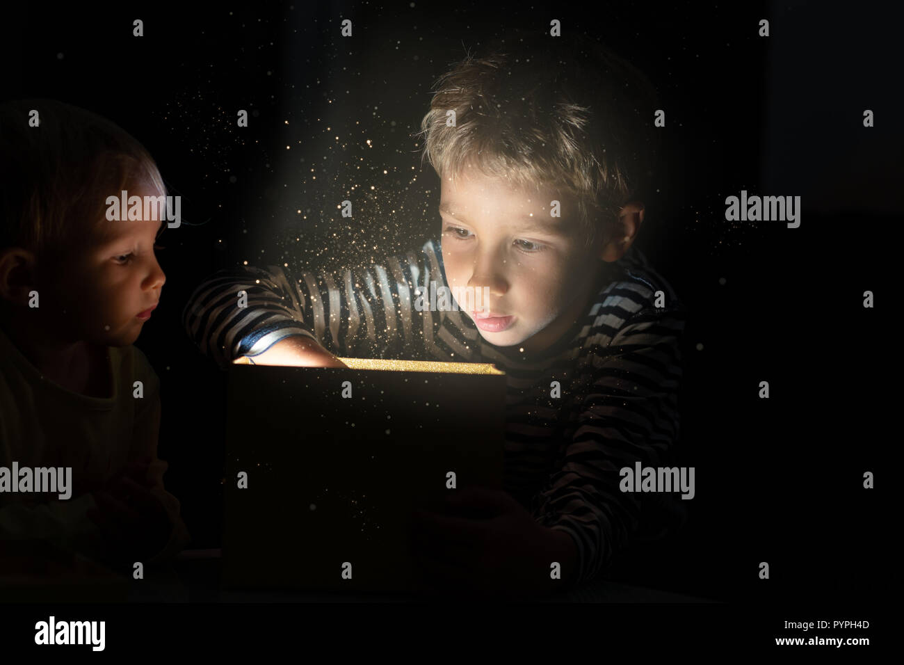 Brother and his little sister with christmas gift box with sparkling light and glitters shinning from it. Stock Photo