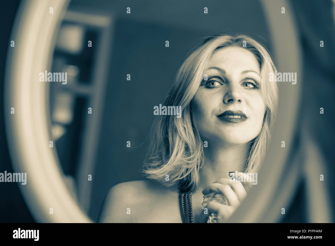 Cinematic portrait of woman sitting on front of mirror in her bedroom and applying perfume. Sultry and sedutive look .Natural lighting and selective f - Stock Image