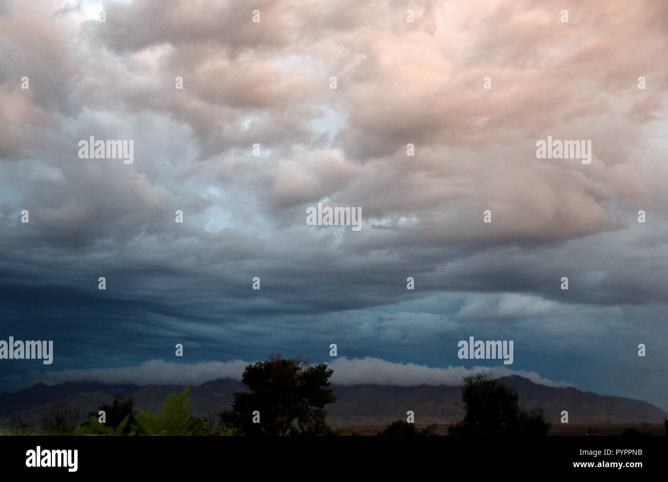 Desert Storm clouds rolling in multi color waves and levels in Arizona - Stock Image