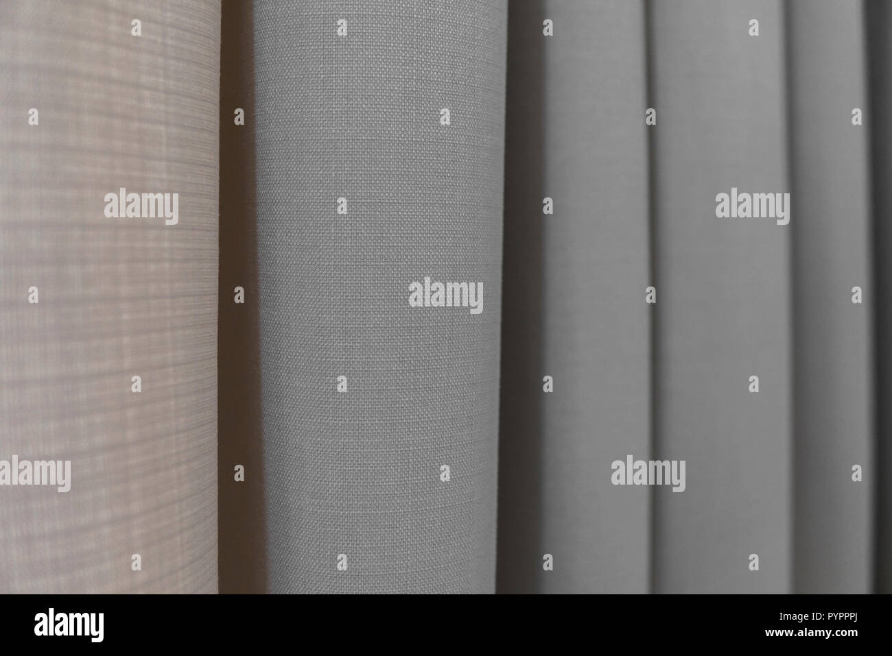 Close-up view of bright curtain in thin and thick vertical folds made of dense fabric.Textured abstract backgrounds and wallpapers.Materials and textiles. - Stock Image