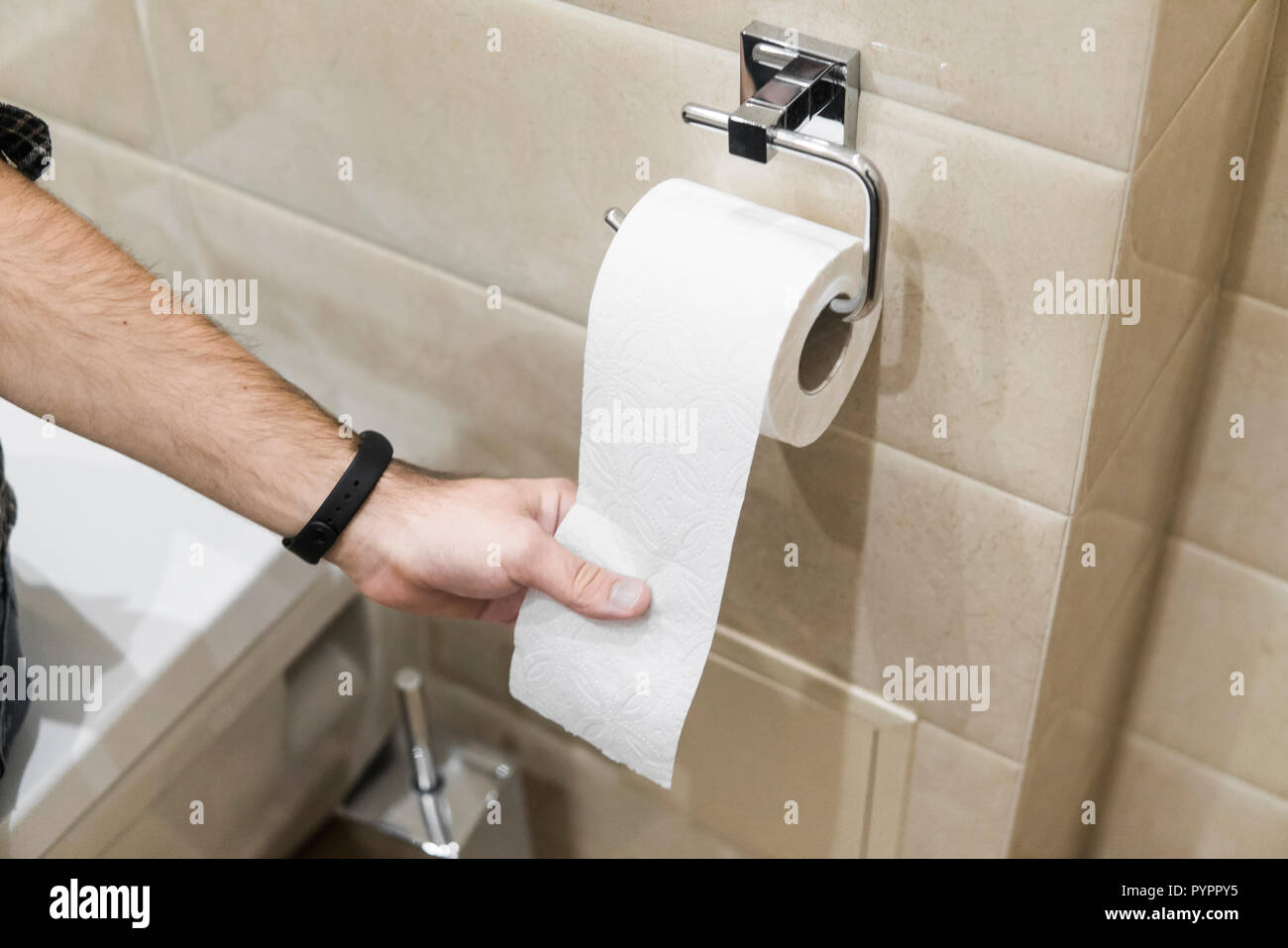 Close-up roll toilet paper in restroom with hand pulling Stock Photo