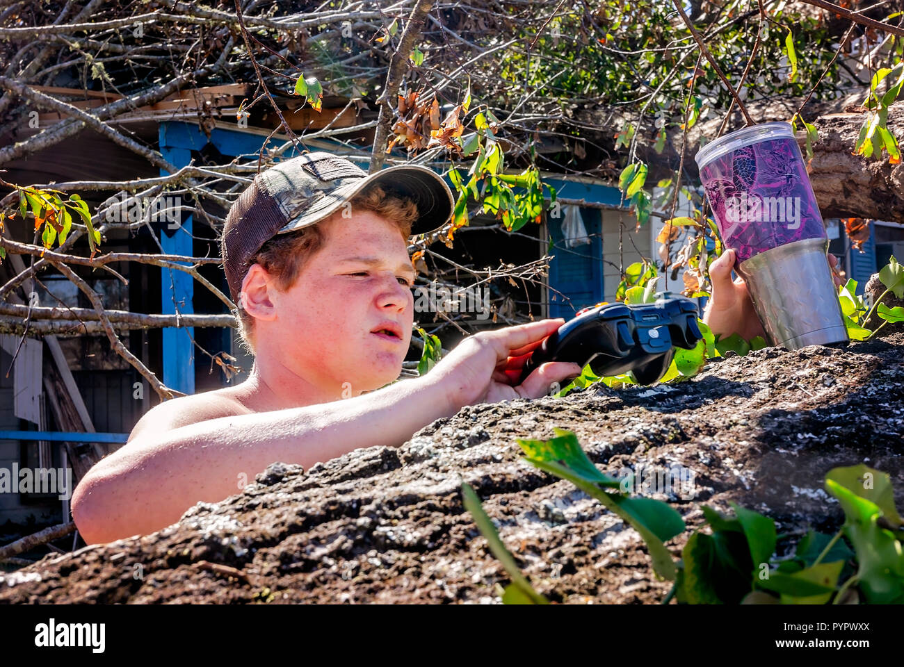 Jayden Davis, 14, examines a game controller he retrieved from his destroyed home after Hurricane Michael, Oct. 21, 2018, in Grand Ridge, Florida. - Stock Image