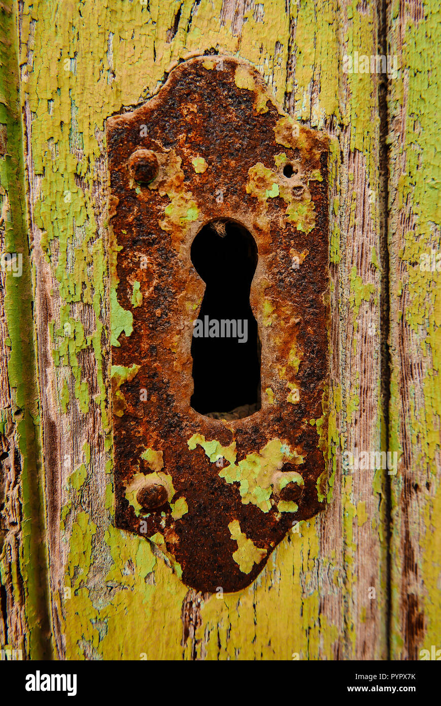 Old rusty keyhole in wooden door with peeling paint on Calle Marques De Cubas in the village of Jacarilla, Spain Stock Photo