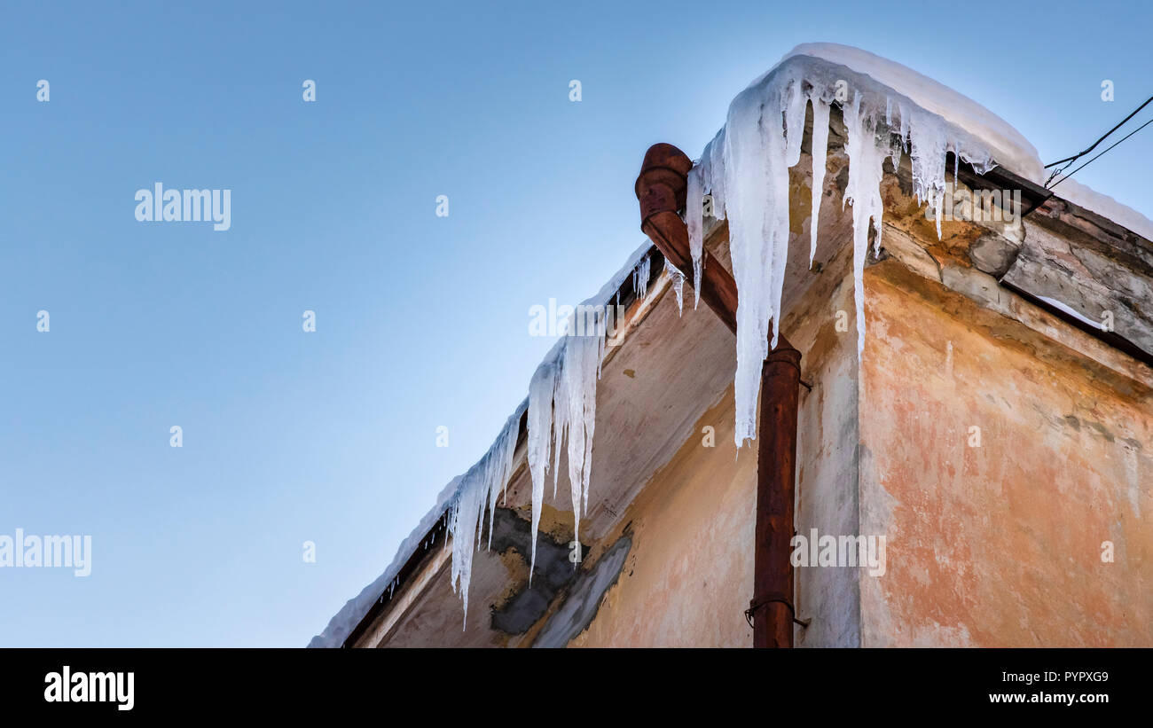 Icicles hang from roof of building. Danger for passers, threat of death and injury from icicles. Winter threats. Banner 16x9 format with copy space - Stock Image