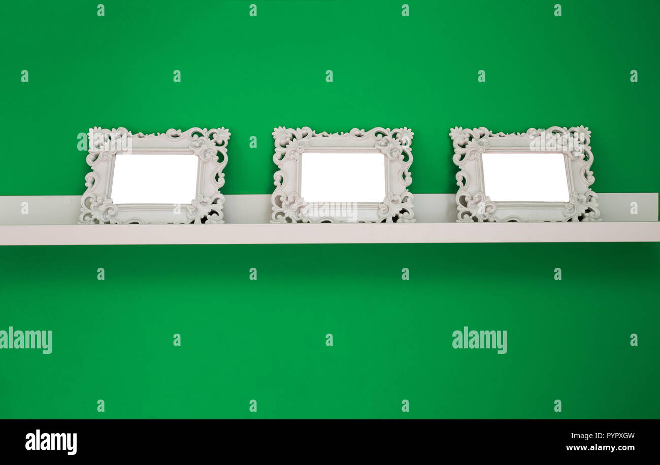 three white empty photo frames on a green wall and wooden shelf, isolated, space for text or photo - Stock Image