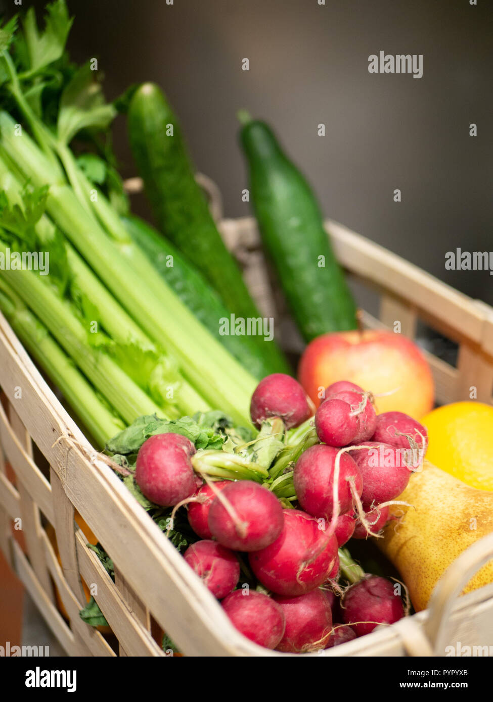wooden basket, filled with radish, celery, cucumber, pears and apples - Stock Image
