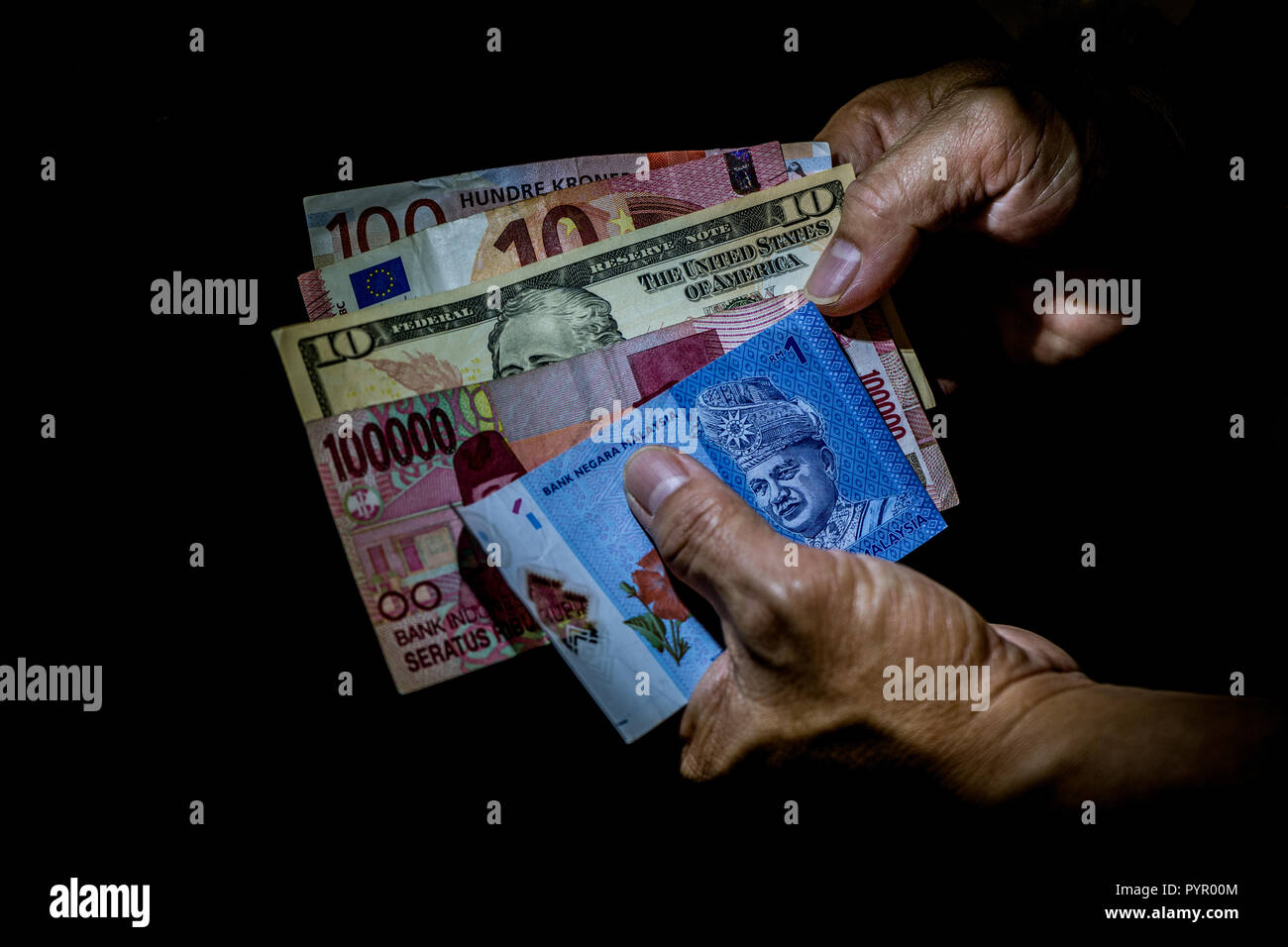 Multi national currencies in a hand of a person. Concept of international traveler finances. - Stock Image