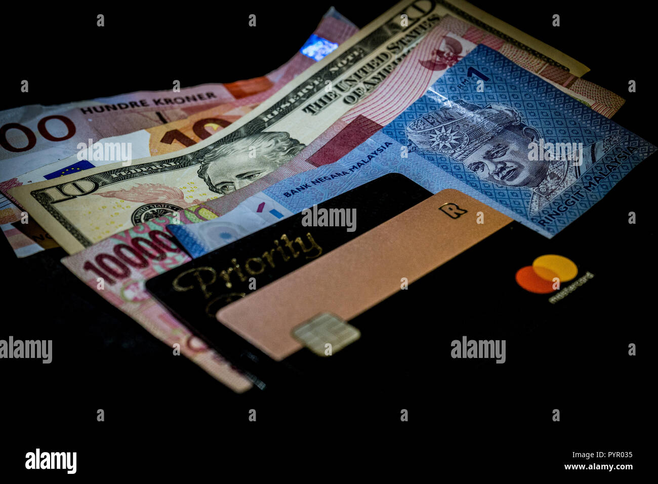 Multi national currencies together with Revolut Mastercard and Priority Pass card for airport lounge access. Concept of international traveler finance - Stock Image