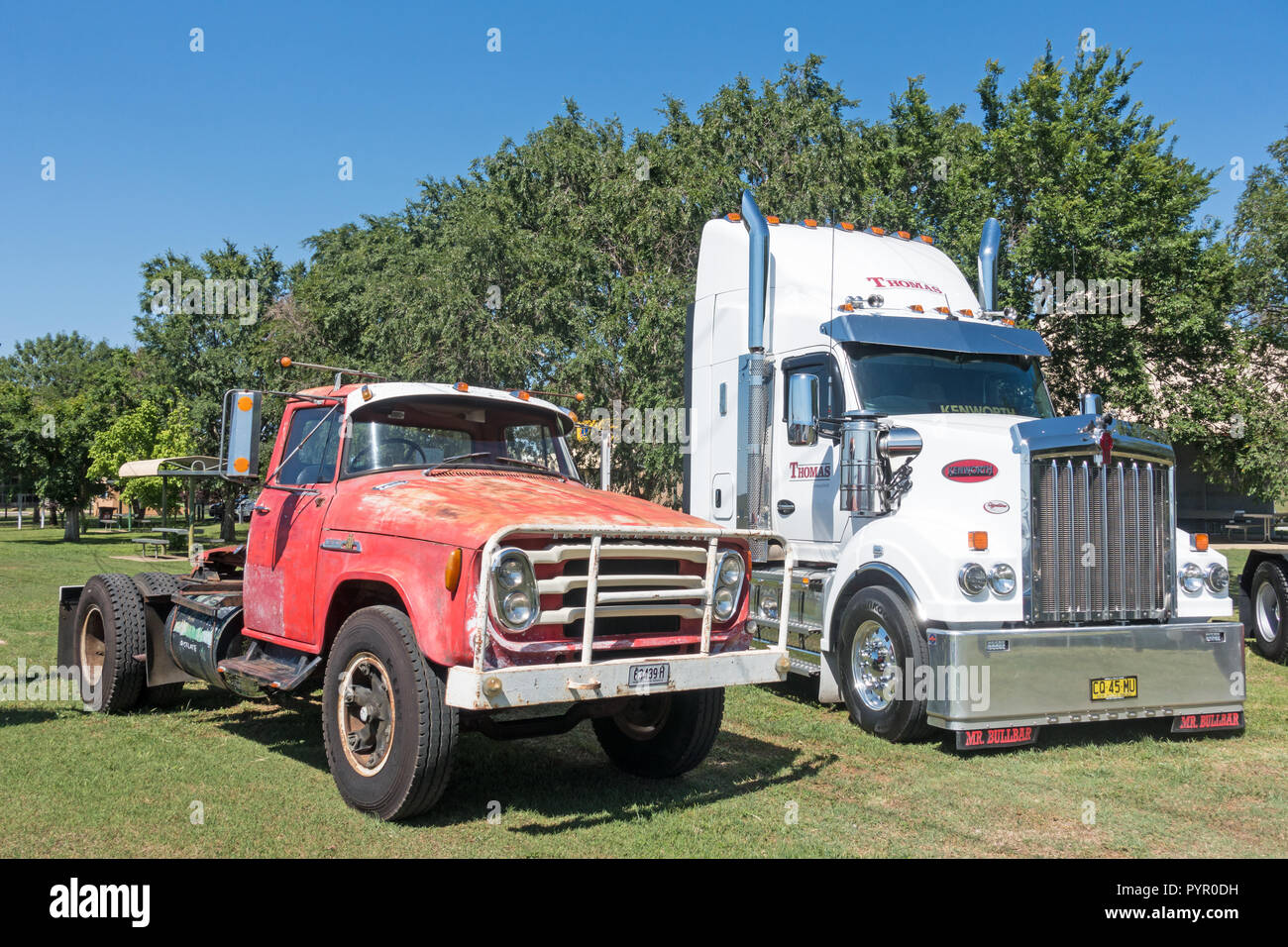 Old and new trucks. International AB 180 and a long nose Kenworth. - Stock Image
