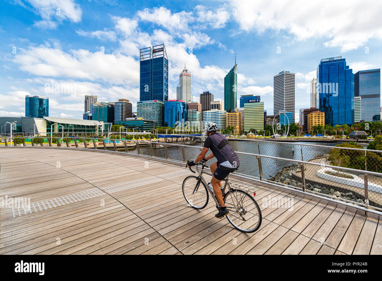 A man cycling over Elizabeth Quay Bridge with a view of Perth city in the background. Elizabeth Quay, Perth, Western Australia - Stock Image
