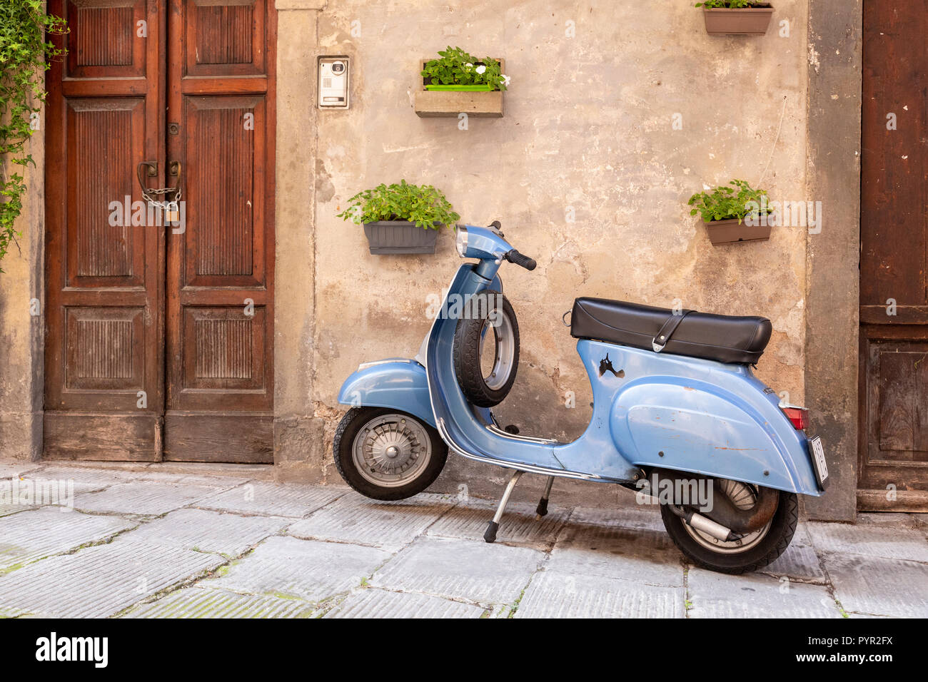 Scooter parked by a wooden door at Lovere on Lake Iseo, italy - Stock Image