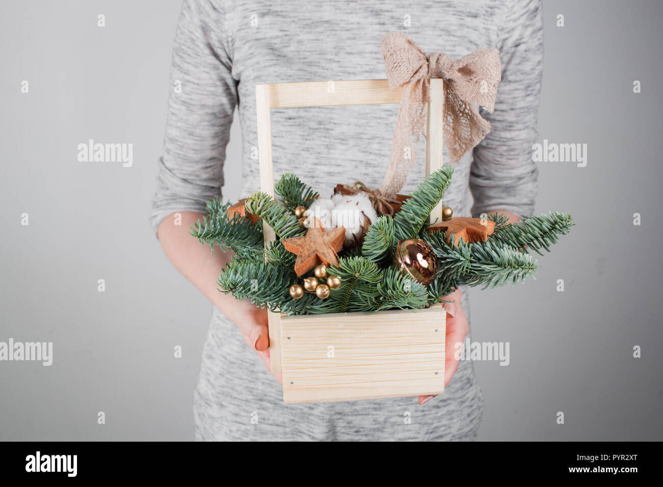 young woman holding christmas compositionin hands in light, seasonal holidays, rustic theme, adorning - Stock Image