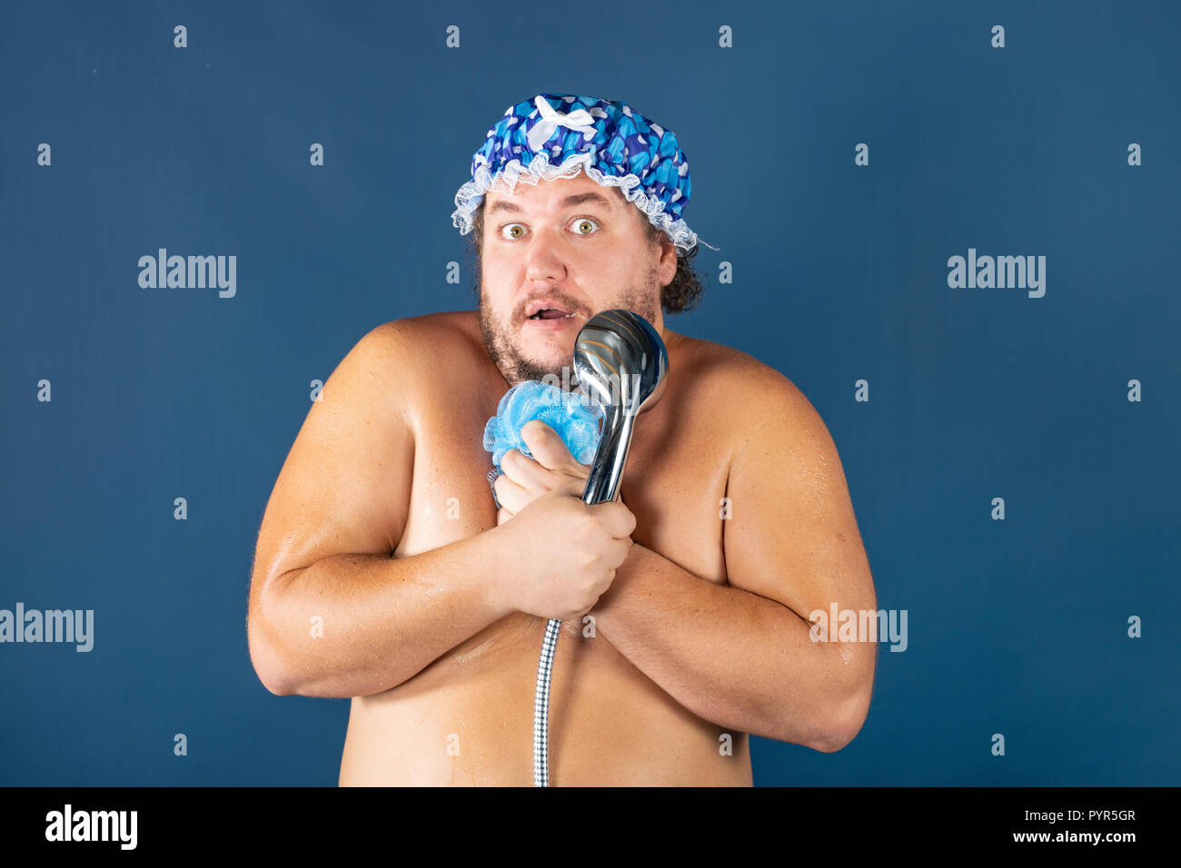 Funny fat man in blue cap sing in the shower. Fun and cleanliness - Stock Image
