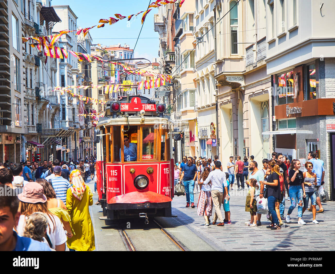 A tram crossing the bustling Istiklal street, adorned with pennants of the Galatasaray Sports Club. Beyoglu district, Turkey. - Stock Image