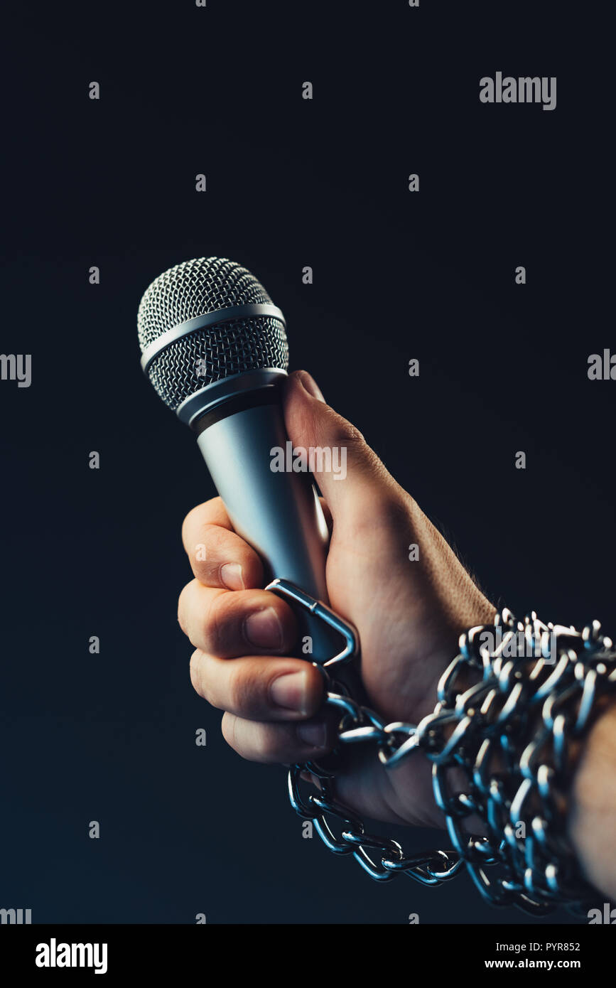 Freedom of the press and journalism, conceptual image with microphone in male hand tied with chains, low key image - Stock Image