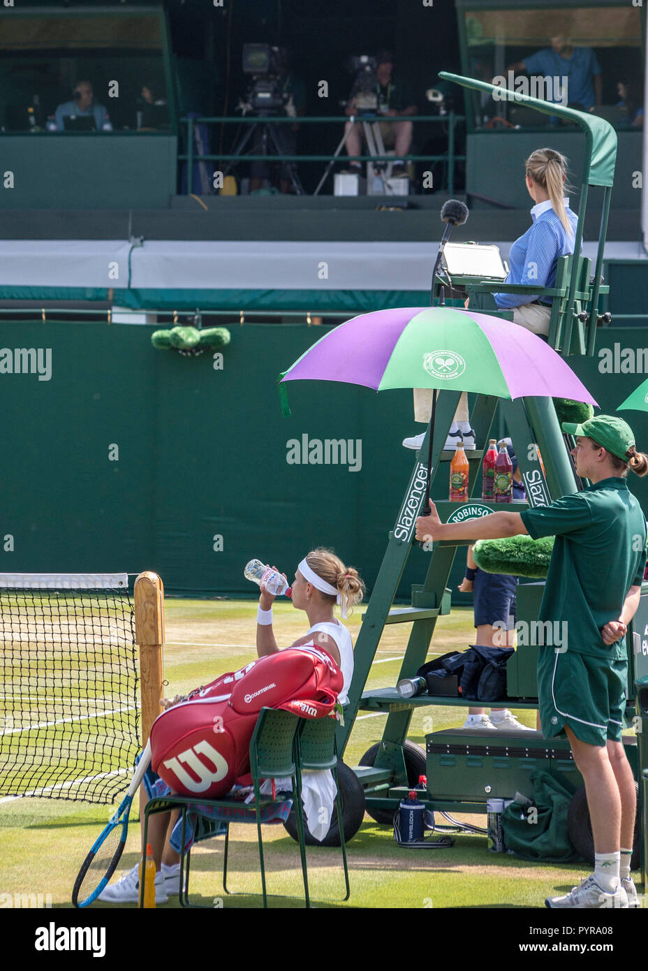 wimbledon tennis match umpire sitting in umpires chair above the players - Stock Image