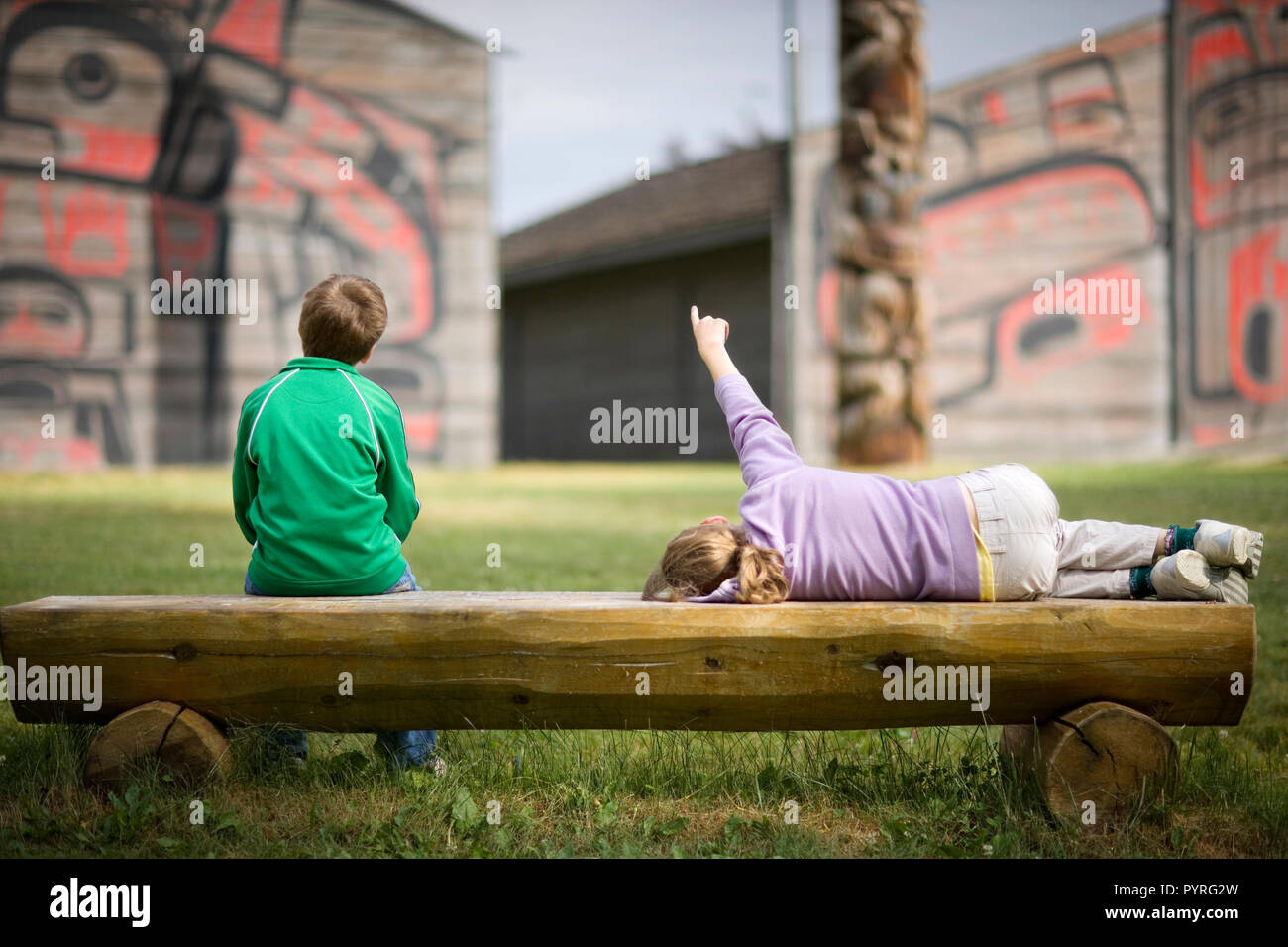 Two children sitting on a wooden bench. - Stock Image